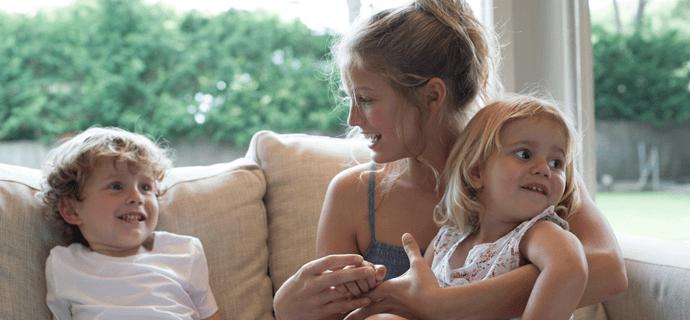 Девушка с двумя маленькими детьми на диване