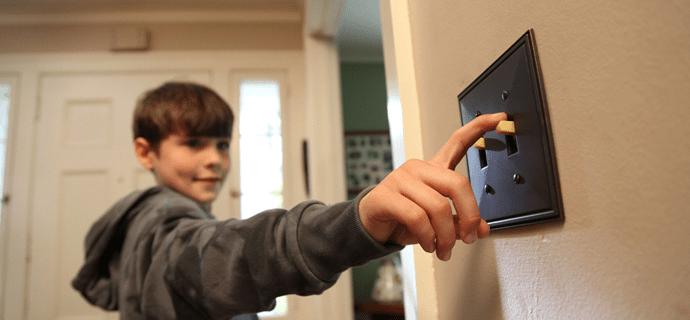 Мальчик щелкает выключатель