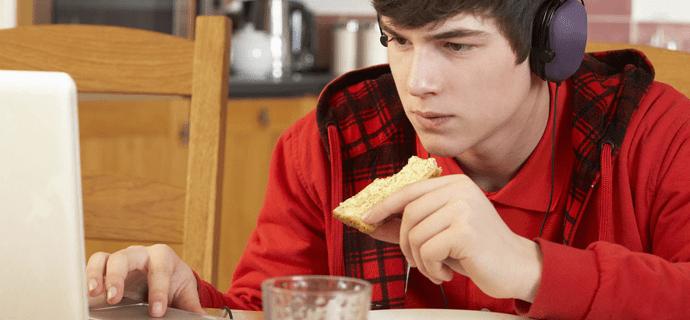 Подросток ест за компьютером