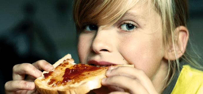 Девушка ест утренний тост с джемом