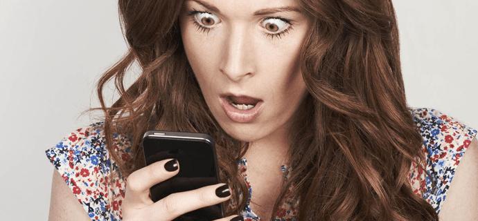Девушка в шоке смотрит на смартфон