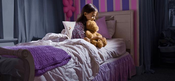 Девочка проснулась ночью и сидит на кровати с мишкой