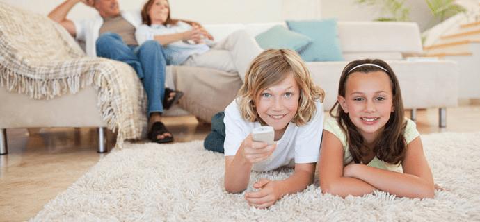 Дети лежат на ковре перед телевизором