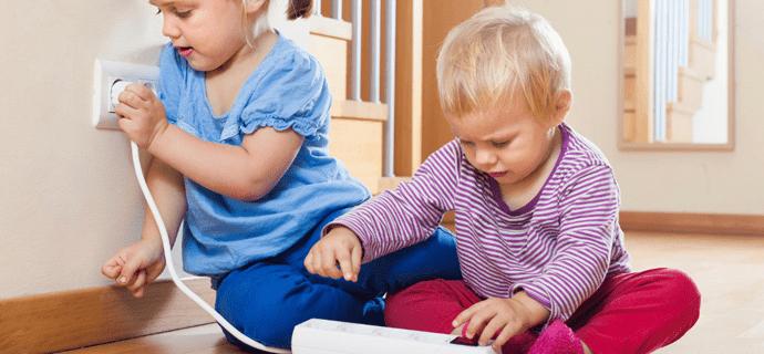 Дети играют с удлинителем у розетки