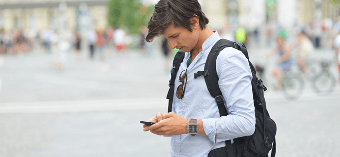 Молодой человек проверяет смартфон