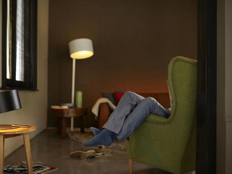 Светильник в комнате, человек сидит в кресле