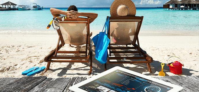 Семья в отпуске у моря, рядом планшет